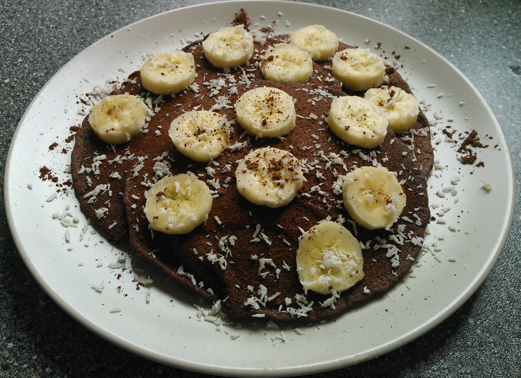 Schokopfannkuchen mit Bananenscheiben und Kokosraspeln belegt