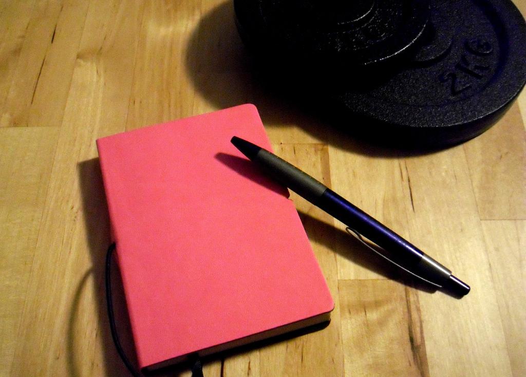 Trainingstagebuch mit Kugelschreiber und Hantelscheibe