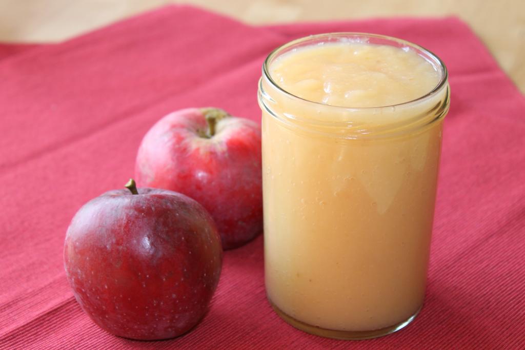 Selbstgemachtes Apfelmus ohne Zuckerzusatz im Einmachglas, zwei Äpfel
