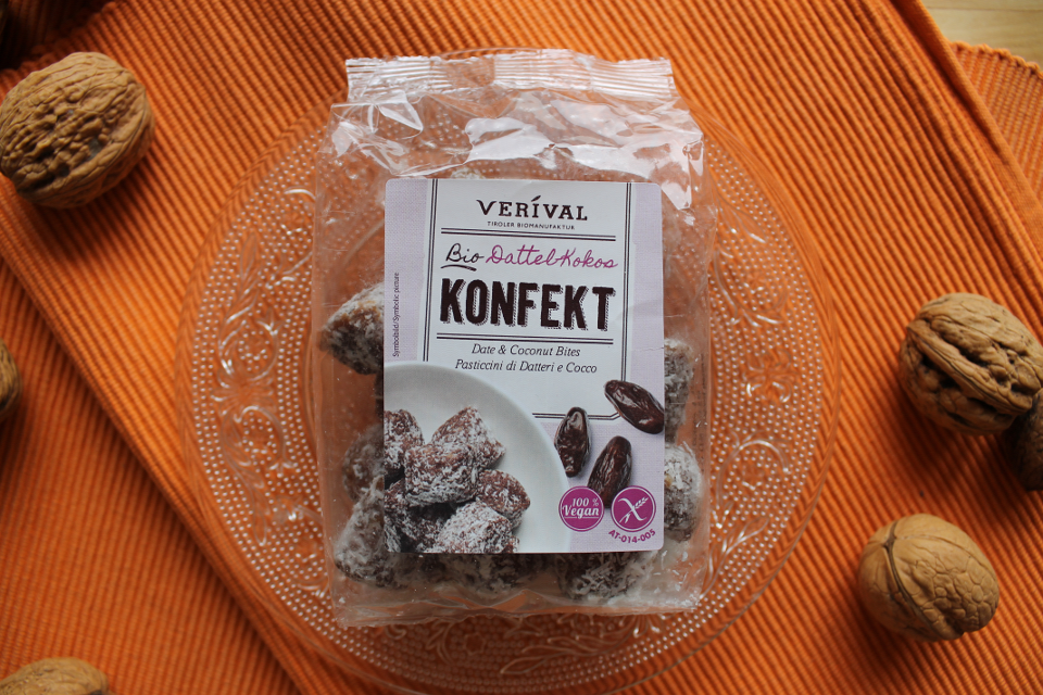 Vorderes Etikett und Verpackung mit Inhalt von Dattel-Kokos Konfekt von Verival auf einem Teller mit orange-farbigen Hintergrund