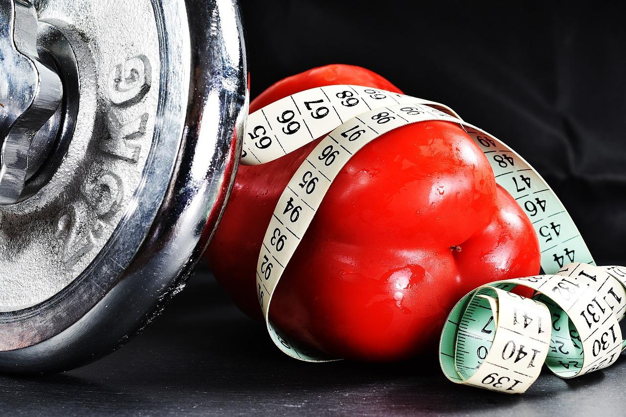 Gewichte, rote Paprika mit Körpermaßband umwickelt