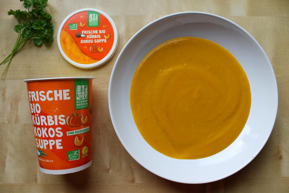 Leere Produktschachtel, auf einem Teller angerichtet Kürbis-Kokos-Suppe von Küchenbrüder