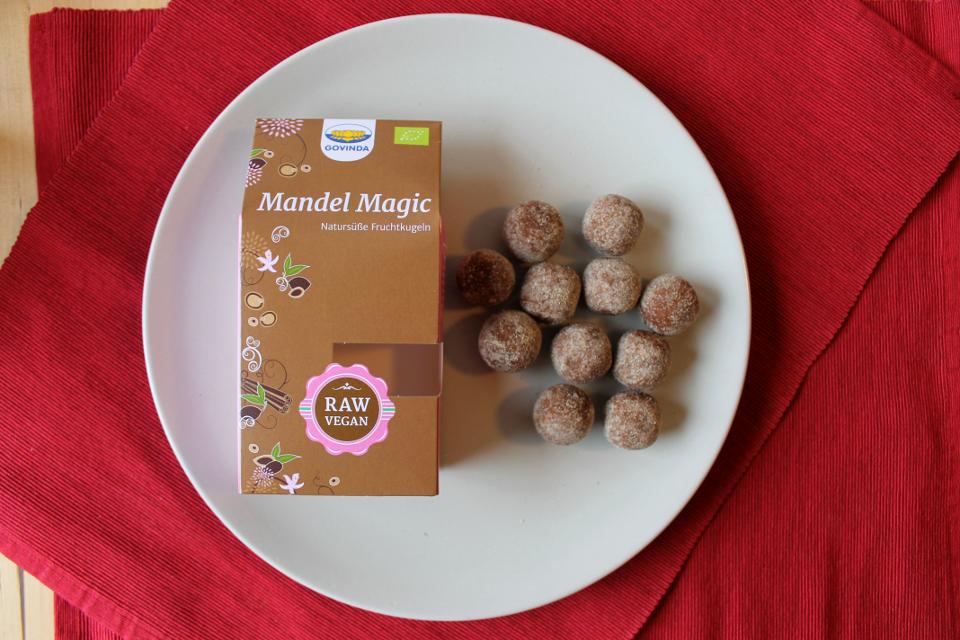 """Fruchtkugel """"Mandel Magic"""" von Govinda, links Verpackung, rechts Fruchtkugeln"""