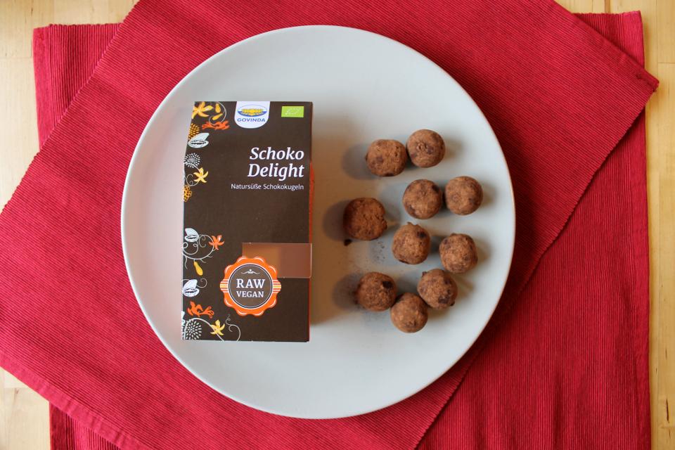 """Schokokugel """"Schoko delight"""" von Govinda, links leere Verpackung, rechts Schokokugeln"""