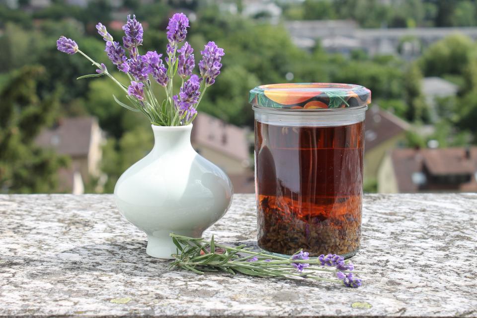 Lavendelblütentinktur im Glas mit eingelegten Lavendelblüten, Lavendelstrauß in der Vase